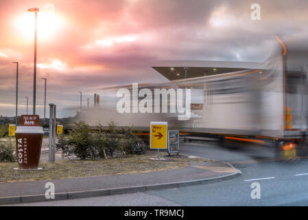 A large Articulated Lorry pulls onto a garage forecourt, as the sun illuminates storm clouds gathering in the sky above. - Stock Photo