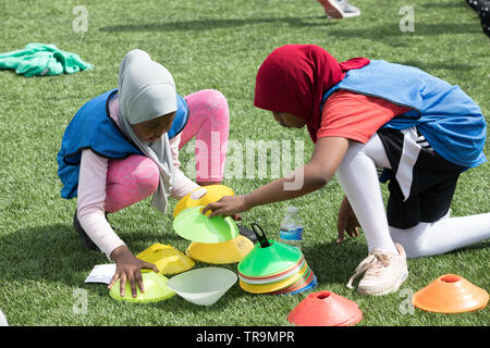 Two girls in Muslim Hijabs prepare to play football on an astroturf training pitch with marker cones. - Stock Photo