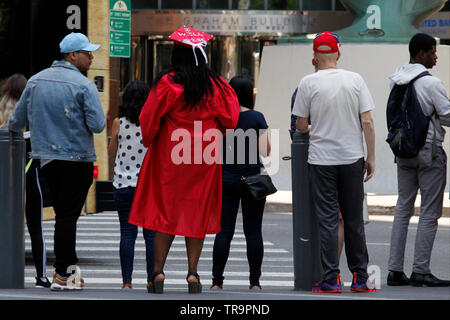Philadelphia, PA, USA - May 31, 2019: A recent graduate in a red cap and gown waits to cross the street downtown on a late spring day. - Stock Photo