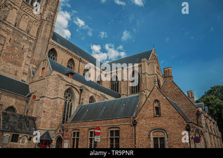 Close-up of brick walls and roofs from a church, against blue sunny sky at Bruges. Charming town with canals and old buildings in Belgium. - Stock Photo