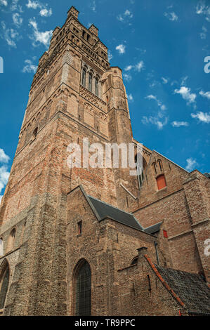Close-up of brick walls and roofs from a church against blue sunny sky. Charming town with canals and old buildings in Belgium. - Stock Photo
