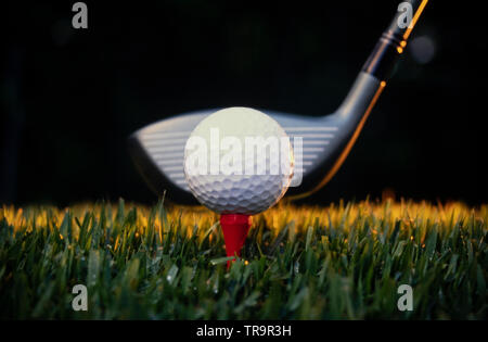 A white golf ball on a red tee in manicured grass. A metal driver is behind the ball - Stock Photo