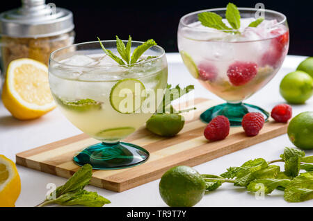 Mojito and raspberry mojito rum cocktail drinks with ingredients, limes, lemons, mint, brown sugar and raspberries. Concept for restaurants, food and - Stock Photo