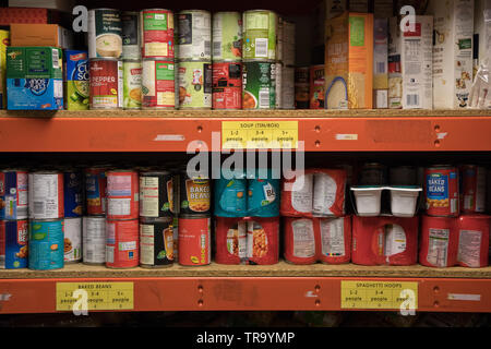 Tins of food stored on shelves at a food bank in Wembley, Greater London - Stock Photo