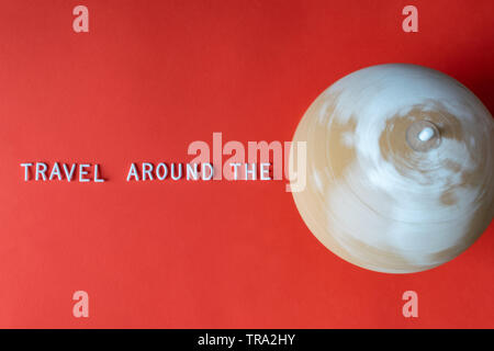 Spinning cork globe in motion with text 'Travel around the' on red background. Close up, Traveling concept. - Stock Photo