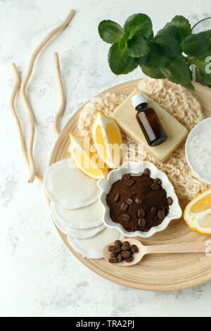 Aroma spa set. Coffee scrub, coffee grains, coffee spa salt, lemon, essential oil, soap on wooden plate and gray background top view copyspace, wellne - Stock Photo