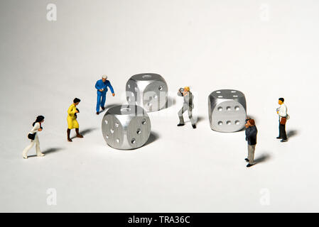 Group of Miniature Photographers take Pictures of three silver dice - Stock Photo