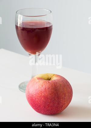 Red apple on wine in glass background, - Stock Photo
