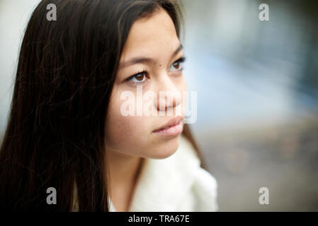 Portrait of a beautiful young teenage Asian girl looking up