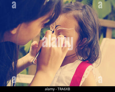 Close up of a young woman applying face painting on a cute little girls face at a birthday party - Stock Photo