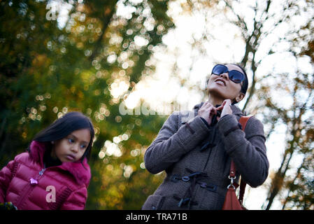 Beautiful low angle portrait of an affluent Asian mother walking outside in a park with her young daughter in autumn sunshine - Stock Photo