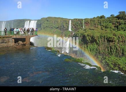 Many Visitors on the Lookout Balcony of Brazillian Side Iguazu Falls Impressed by the Rainbow, Foz do Iguacu, Brazil, South America - Stock Photo