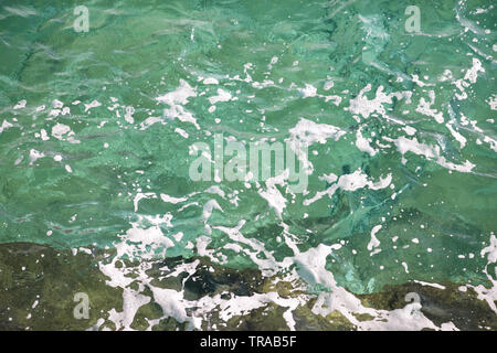 Turquoise green seawater with sea foam as background, close up. Surface of sea with waves, splash, foam and bubbles, blue abstract texture. - Stock Photo