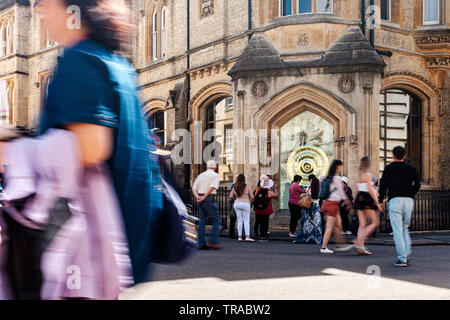 Tourists in Cambridge photograph and walk past the The Taylor Library and the Corpus Clock on the northwest corner of Corpus Christi College. - Stock Photo