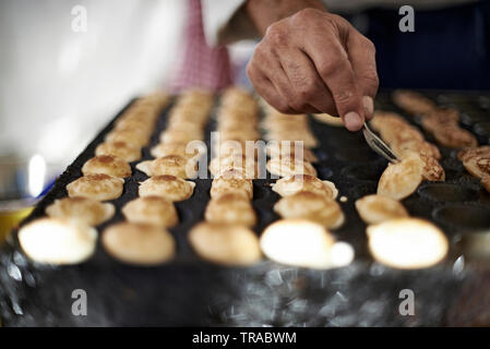 Chef preparing small Dutch pancakes called poffertjes in a market stall outdoors in the city centre of Amsterdam - Stock Photo