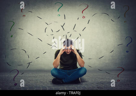 Confused and tired young man seated on the floor keeps hands to forehead looking down thoughtful surrounded by different tasks to solve as having many - Stock Photo