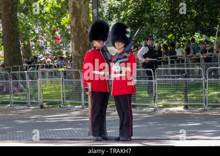 Royal Guards in red and black uniform and bearskin hats stand in The Mall during the annual Trooping the Colour military parade, London UK - Stock Photo