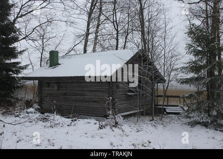 Traditional old-fashioned sauna log cabin in Finland in the winter with snow - Stock Photo