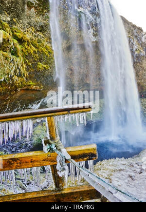 View of the icy walking path next to Seljalandsfoss waterfall in winter in Iceland. - Stock Photo