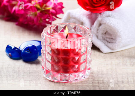 spa concept, red candle with blue stones, flowers and towel on wooden background, - Stock Photo