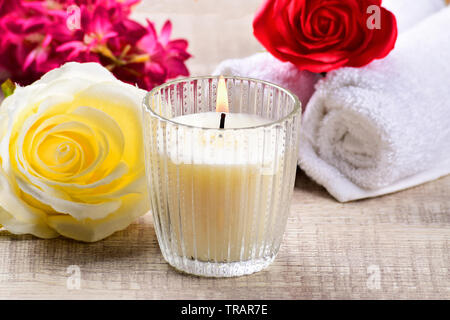 white candle with yellow flower on wooden background, scented candle, spa composition. - Stock Photo