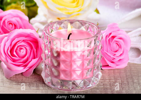 pink rose candle with flowers and towel on wooden background, - Stock Photo