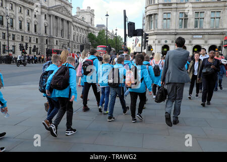 Rear view of primary school students on day trip outside Houses of  Parliament Square near pedestrian crossing on Bridge Street West London SW1 UK GB - Stock Photo