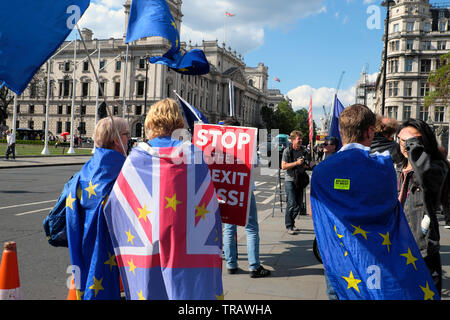 Rear view of protest in street outside the Houses of Parliament wearing Union Jack & European Union flags & Stop Brexit Mess London UK  KATHY DEWITT - Stock Photo
