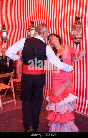 Torrevieja, Spain - June 1, 2019: Couple of mature people in traditional spanish clothe dancing together on Sevillian fair - Stock Photo