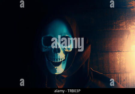 Halloween costume ghost scary skeleton wearing a hooded coat / Grim reaper with skull in black hood on the dark - Stock Photo