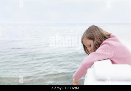 Little cute girl (7 years old) is standing against the sea in a pink outfit. Selective focus. - Stock Photo