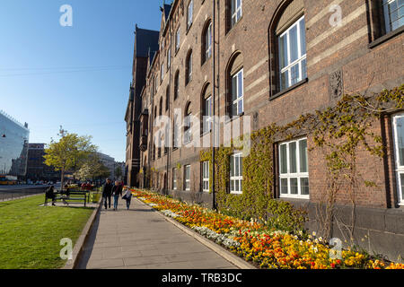 People walking in the street with beautiful flowers, next to the Tivoli amusement park in the city of Copenhagen - Stock Photo