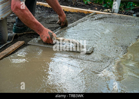 Hand builder with trowel leveling concrete, spreading poured. Some motion blur present - Stock Photo