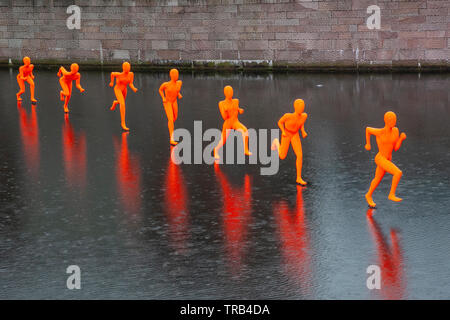 Liverpool,UK. 2nd June, 2019 UK Weather: Wet, rainy conditions on art work in Canning Dock. 'The Runner' created by Faith Bebbington, is one of the at the weekend River Festival, and features several neon illuminated orange figures apparently running on water. Credit: MediaWorldImages/AlamyLiveNews - Stock Photo