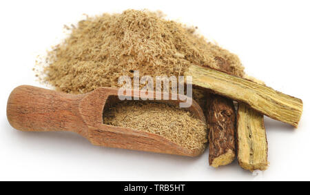 Liquorice stick and ground in a wooden scoop over white ackground - Stock Photo