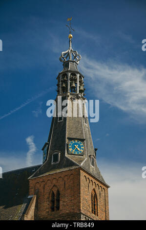 Close-up of pointed steeple roof in a church made of bricks and golden clock at Weesp. Pleasant village full of canals and green in Netherlands. - Stock Photo