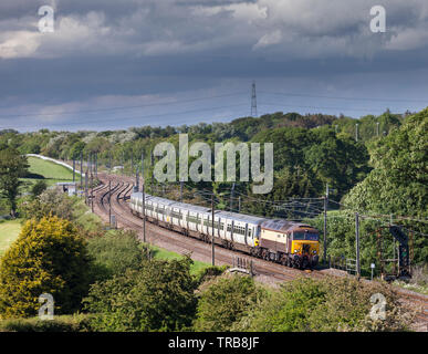 Rail Operations Group class 57 diesel locomotive on the west coast main line hauling off lease class 365 electric multiple units for storage - Stock Photo