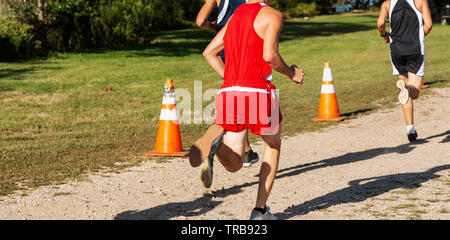 A high school boy running in a cross counrty race on a gravel path with the sun at his back making a large shadow in front. - Stock Photo