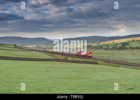 DB cargo class 66 locomotive on Shap bank, West Coast Main line, Cumbria with a northbound freight train of empty lime containers - Stock Photo