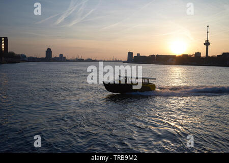 Amazing wide landscape of the river Maas in the city centre of Rotterdam during an incredible sunset with dramatic sky - Stock Photo