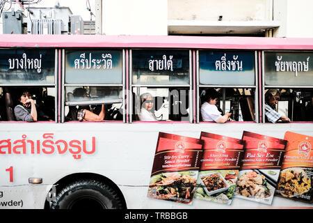 Thai Locals on a Bus in Bangkok, Thailand - Stock Photo