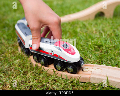 Child Playing with a Wooden Toy Brio-style Bullet Express Train - Stock Photo