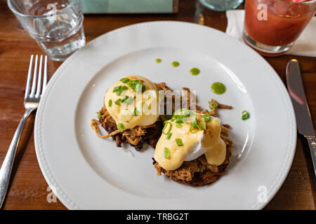 Pulled pork served on fried potato pancakes topped with poached egg and garnished with hollandaise sauce and fresh green onion aka 'farmers Benedict' - Stock Photo