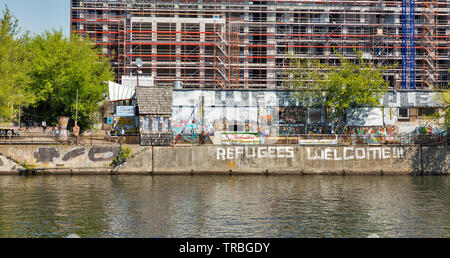BERLIN, GERMANY - APRIL 18, 2019: People visit YAAM night club with sign Refugees Welcome! along the Spree riverbank. Berlin is the capital and larges - Stock Photo