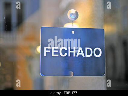 Closed sign in portuguese language on the glass - Stock Photo