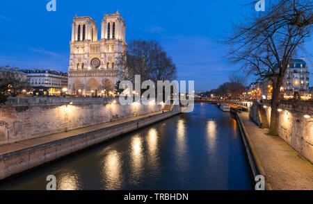 Evening view of the Notre Dame Cathedral, Paris France, during the winter from the embankment of the Seine River.