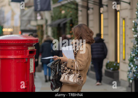 London, UK - 17, December 2018: Woman drop letter in the red color traditional victorian British postbox standing on the London street. - Stock Photo