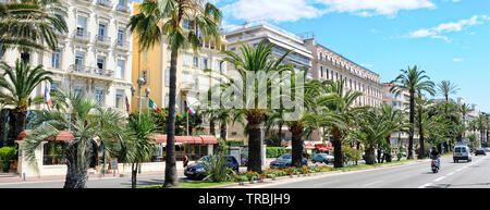 Panoramic wide image Nice city, palm lined trees urban road, architecture, blue sky sunny day, famous travel destinations for vacationers, travellers, - Stock Photo