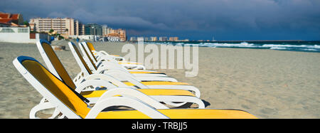 Horizontal image cropped view yellow blue color empty sunbeds deck-chairs in a row on the sandy beach, La Manga del Mar Menor seaside during stormy we - Stock Photo