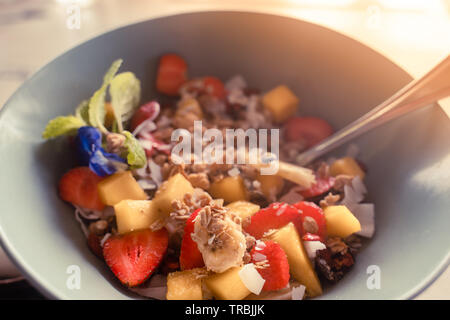 Healthy breakfast porridge concept: oatmeal with coconut flakes, strawberry, banana and mango pieces served with Greek yogurt and natural honey - Stock Photo